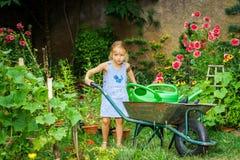 Gullig liten flicka som arbeta i trädgården i trädgården Arkivfoto