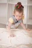 Gullig liten flicka som arbetar med kavlen Arkivfoto