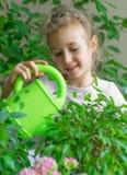 Gullig liten flicka som bevattnar blommor Royaltyfri Fotografi