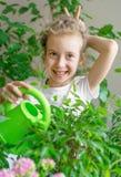 Gullig liten flicka som bevattnar blommor Royaltyfria Foton
