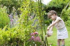 Gullig liten flicka som bevattnar blommor i trädgård Royaltyfria Bilder