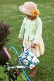 Gullig liten flicka som bevattnar blommor i trädgården Royaltyfria Foton