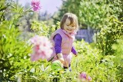 Gullig liten flicka som bevattnar trädgården Arkivbild