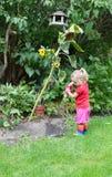 Gullig liten flicka som bevattnar växter Royaltyfria Foton
