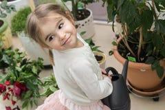 Gullig liten flicka som bevattnar växter i hennes hus royaltyfria foton