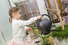 Gullig liten flicka som bevattnar växter i hennes hus arkivfoto