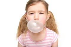 Gullig liten flicka som blåser en bubbla från tuggummi Fotografering för Bildbyråer