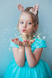 Gullig liten flicka som blåser magiskt damm Fotografering för Bildbyråer