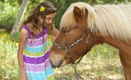 Gullig liten flicka som daltar hennes ponny Arkivbild