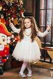 Gullig liten flicka som dansar nära julgranen och nötknäpparen Arkivbilder