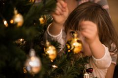 Gullig liten flicka som dekorerar julgranen fotografering för bildbyråer