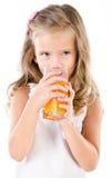 Gullig liten flicka som dricker isolerad orange fruktsaft royaltyfri fotografi