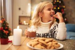 Gullig liten flicka som dricker kakao och hemma äter kakan royaltyfri foto