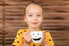 Gullig liten flicka som dricker pumpasoppa ut ur en kopp med den anthropomorphic smileyframsidan för allhelgonaafton Begreppsmäss royaltyfri foto