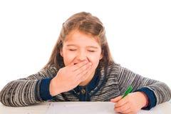 Gullig liten flicka som gäspar, medan skriva Arkivbilder
