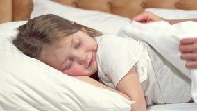 Gullig liten flicka som går att sova i hennes säng, moder som stoppar filten stock video