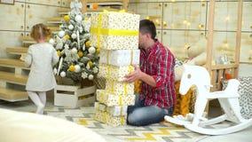 Gullig liten flicka som ger gåvaaskar för att avla nära julgranen hemma stock video