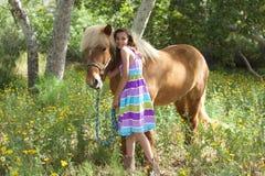 Gullig liten flicka som ger hennes ponny en smyga sig Fotografering för Bildbyråer