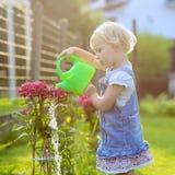 Gullig liten flicka som ger vattenträdgårdblommor arkivbilder