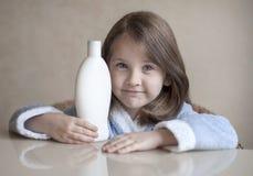 Gullig liten flicka som håller olika vita skönhettoalettartiklar i hennes händer som ser kameran Behandla som ett barn badet, hyg Fotografering för Bildbyråer
