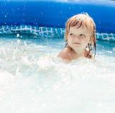 Gullig liten flicka som har gyckel i simbassängen Arkivfoto