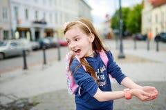 Gullig liten flicka som har gyckel med dricksvattenspringbrunnen på solig sommardag royaltyfria foton