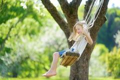 Gullig liten flicka som har gyckel på en gunga, i att blomstra den gamla trädgården för äppleträd utomhus på solig vårdag arkivfoton