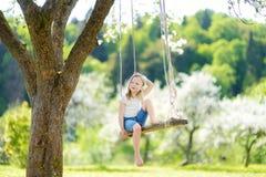 Gullig liten flicka som har gyckel på en gunga, i att blomstra den gamla trädgården för äppleträd utomhus på solig vårdag fotografering för bildbyråer