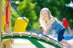 Gullig liten flicka som har gyckel på en lekplats Arkivfoton