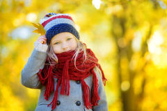 Gullig liten flicka som har gyckel på härlig höstdag Det lyckliga barnet som spelar i höst, parkerar Lövverk för nedgång för unge Royaltyfria Bilder