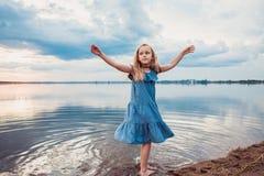 Gullig liten flicka som har gyckel på sjön Arkivbild