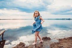 Gullig liten flicka som har gyckel på sjön Arkivbilder