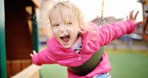 Gullig liten flicka som har gyckel på utomhus- lekplats royaltyfri bild
