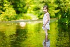 Gullig liten flicka som har gyckel vid en flod Arkivfoton