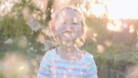 Gullig liten flicka som har roligt blåsa maskrosfrö, medan koppla av på naturen lager videofilmer