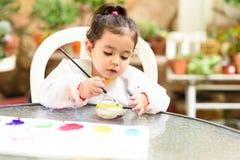 Gullig liten flicka som har roligt och att färga med borsten, att spela och att måla Förskolebarn med målarfärg på trädgården royaltyfri bild