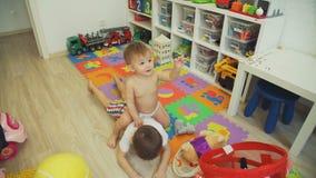 Gullig liten flicka som hemma rider hans broder stock video