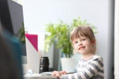 Gullig liten flicka som hemma sitter på worktablen som in camera ser royaltyfri bild