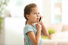 Gullig liten flicka som hemma talar vid mobiltelefonen Royaltyfria Foton