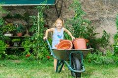 Gullig liten flicka som hjälper hennes moder i trädgården Royaltyfria Foton