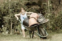 Gullig liten flicka som hjälper hennes moder i trädgården Royaltyfri Bild