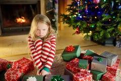 Gullig liten flicka som känner sig olycklig med hennes julgåvor Barnsammanträde vid en spis i en hemtrevlig mörk vardagsrum på Xm arkivfoto