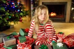 Gullig liten flicka som känner sig olycklig med hennes julgåvor Barnsammanträde vid en spis i en hemtrevlig mörk vardagsrum på Xm arkivbilder