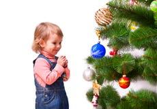 Gullig liten flicka som klär julgranen arkivfoto