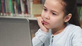 Gullig liten flicka som koncentrerar genom att använda hennes bärbar dator royaltyfria bilder