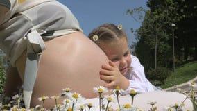Gullig liten flicka som kramar den gravida magen för mammor stock video