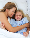 Gullig liten flicka som kramar med henne modern Royaltyfri Foto
