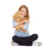 Gullig liten flicka som kramar nallebjörnen Arkivfoton
