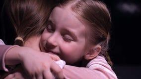 Gullig liten flicka som kramar stramt hennes moder efter det långa avskiljandet, leende på framsida stock video
