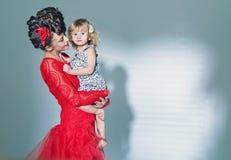 Gullig liten flicka som kramas av hennes moder Arkivbilder
